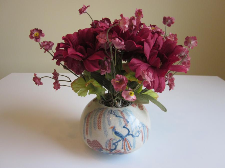 Burgundy Floral Arrangement. Burgundy faux floral arranged in vintage hand-painted ceramic pot with three footed base, pot is 4` H; 9`H x 5-1/2` H overall dimensions.