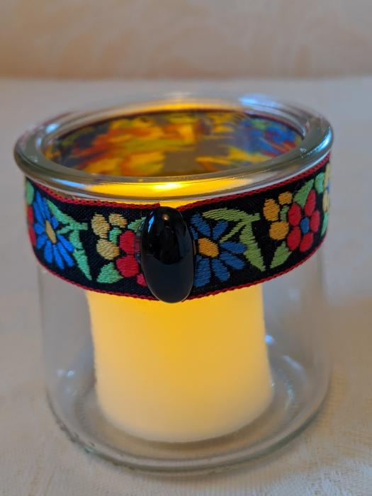 Handcrafted Glass Votive Holder. Recycled glass votive holder decorated with vintage 1970`s embroidered ribbon and a 10mm x 19mm black onyx gemstone cabochon. Candleholder measures 2-1/2 inches diameter x 2-3/4 height. LED battery-powered flameless candle is included. This product is made to order.
