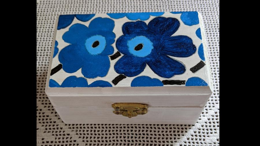 "Hand-painted Blue Poppy Dream Box (Marimekko ""Unikko"" design). Handcrafted pine box, rectangular shape 4-1/2`W x 2-3/4`D x 2-1/2`H, hinged top with brass latch, hand-painted with Marimekko Blue Poppy `Unikko` design, white exterior finish, unfinished natural wood interior.<br /><br />Ideal for storing small objects, jewelry or office supplies on a desk.<br /><br />A Dream Box is meant to serve as <br />a physical reminder<br />that dreams will come true <br />if you search deep within your heart.<br /><br />Write your dream on a piece of paper. <br />Fold the paper and place it in <br />the Dream Box.<br /><br />May your days be filled with rainbows <br />and your nights with stars.<br />"
