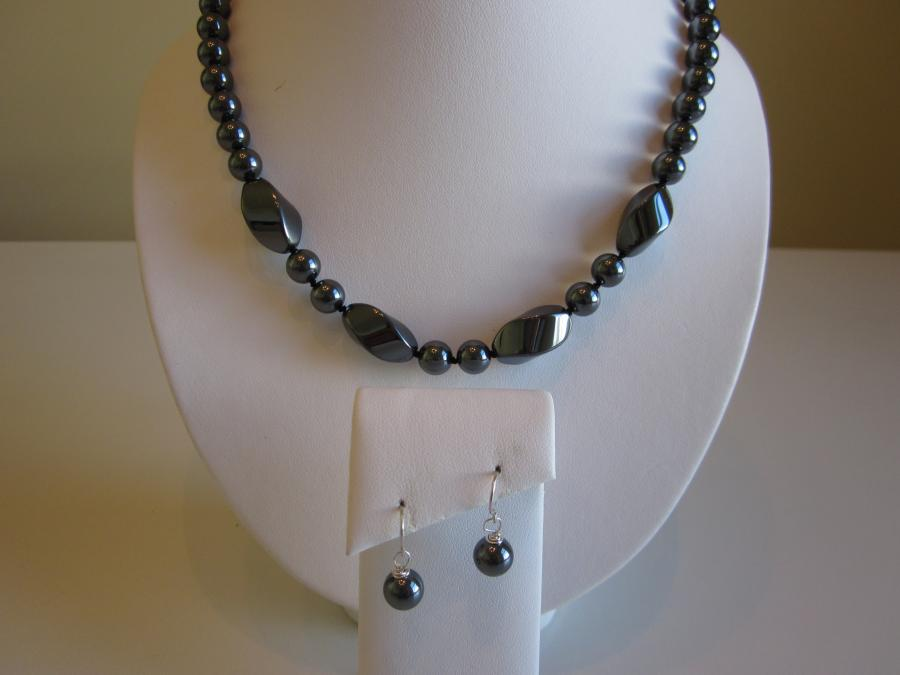 Hematite Demi Parure. 8mm round hematite beaded necklace, hand-knotted on matching black silk cord with a sterling silver lobster claw clasp, 26-inches length. <br /><br />Matching earrings with sterling silver shepherd`s hook earwires for pierced ears.<br /><br />This set was donated to Holy Trinity Orthodox Church of East Meadow, New York for their 2016 Faith, Food & Fellowship Festival Chinese Auction.