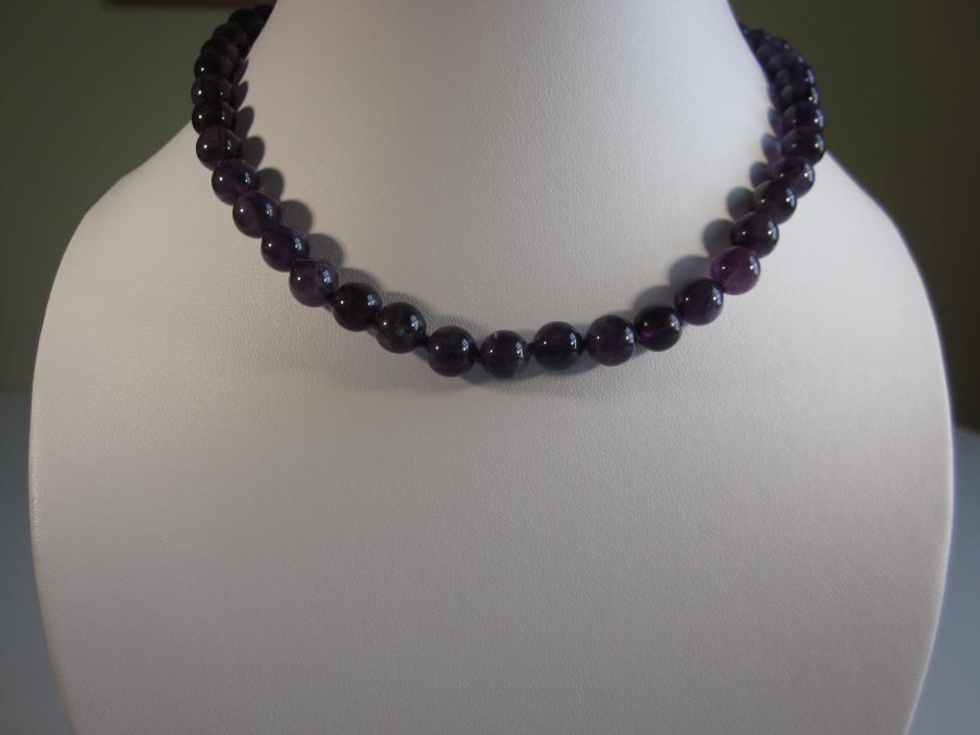 Amethyst Beaded Necklace. 8mm round amethyst beaded necklace, hand-knotted on matching purple silk cord, sterling silver lobster clasp closure, 15-1/2` length.<br /><br />Matching earrings also available.