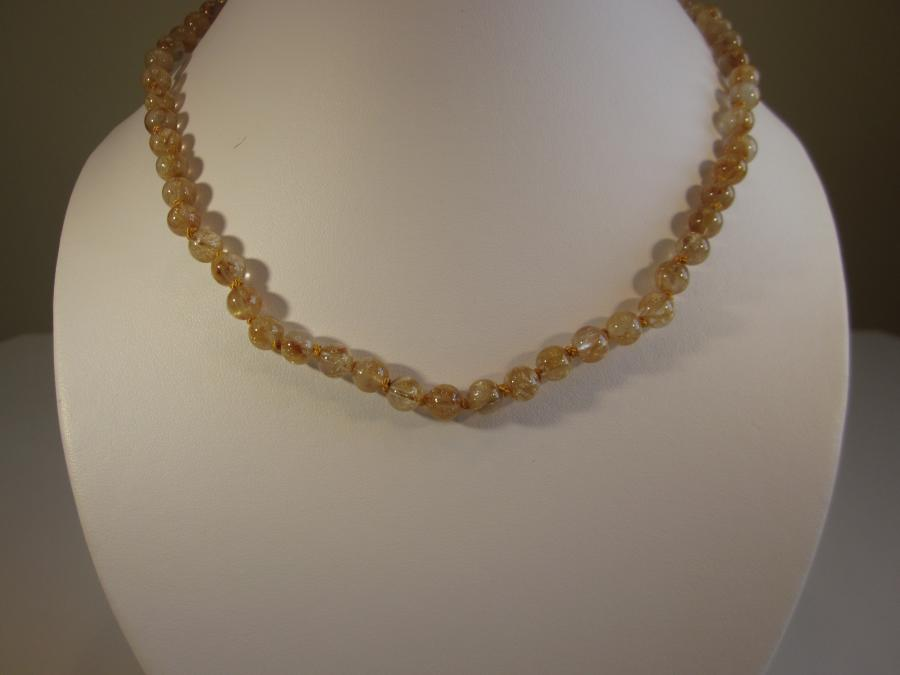 Golden Rutilated Quartz Beaded Necklace. 6.5mm round golden rutilated quartz beaded necklace, hand-knotted on matching gold silk cord, finished with a round gold-filled filigree box clasp, 18-inches length.<br /><br />Matching earrings also available.