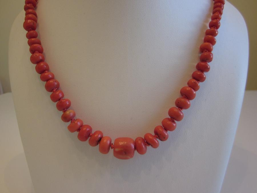 Graduated Faux Coral Necklace. Graduated disc-shaped faux coral beaded necklace hand-knotted on matching orange silk cord, 27` length with a oversized gold-plated lobster clasp closure.