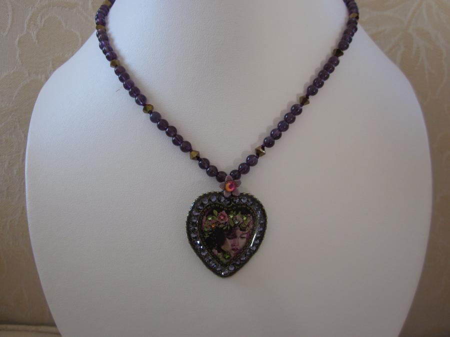 Heather On Earth Amethyst Necklace. This is a special remembrance necklace: Israeli designer Michal Negrin created the crystal heart pendant for HeatherOnEarth.org, a non-profit organization supporting music therapy to pediatric patients who struggle to cope with hospitalization and illness. This heart is created in memory of Heather Fessler, who passed away in 1985 at the age of 4. Her mother Geri made it her life mission to bring the gift of music to sick children in hospitals in the United States and around the world.<br /><br />Edessa Studio designed the necklace using Michal Negrin`s heart as a centerpiece with hand-knotted 4mm amethyst and Swarovski crystal beads as the `chain`. Necklace length is 28-inches without a clasp. Necklace is designed to be slipped over the wearer`s head.