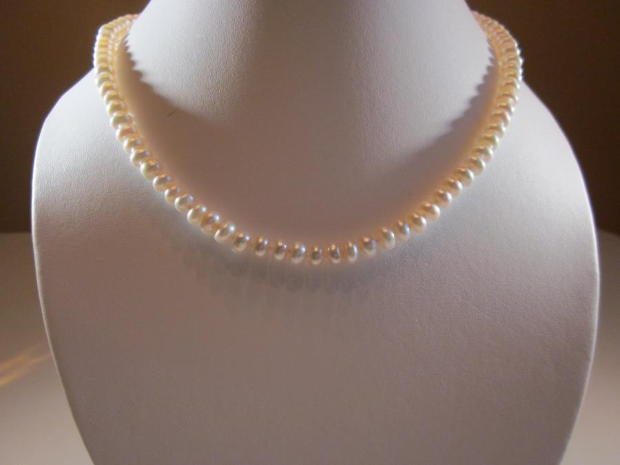 White Cultured Freshwater Pearl Necklace. White cultured freshwater pearl necklace, handknotted on white silk cord, 18 inches length, sterling silver pearl clasp